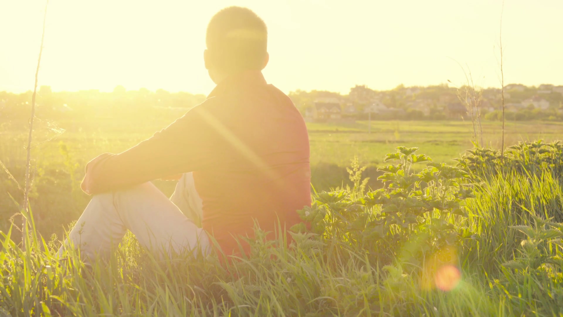 videoblocks-back-view-of-a-yang-man-sitting-on-a-green-meadow-at-sunset-blurred-background-backlight_hbnpr_j_thumbnail-full01
